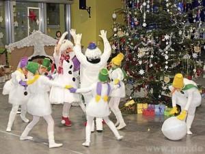 Schneeflocken und Schneemänner in Aktion rund um den Weihnachtsbaum
